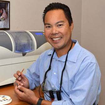 Dr. Joe N.T. Nguyen DDS customizing a dental piece for a patient