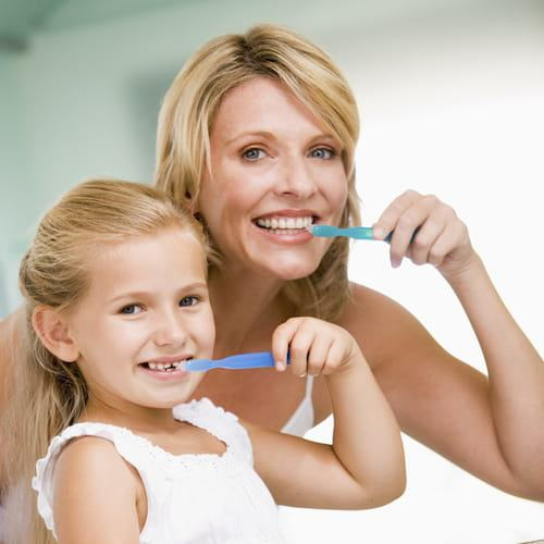 Mom and daughter brushing teeth to show that this dentist in Poway, CA offers Family Dentistry