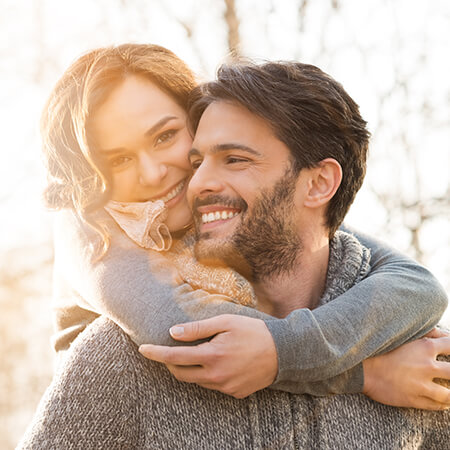 A couple with beautiful smiles laughing together